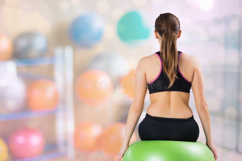 妇女背面图坐健身球在健身房 免版税库存图片