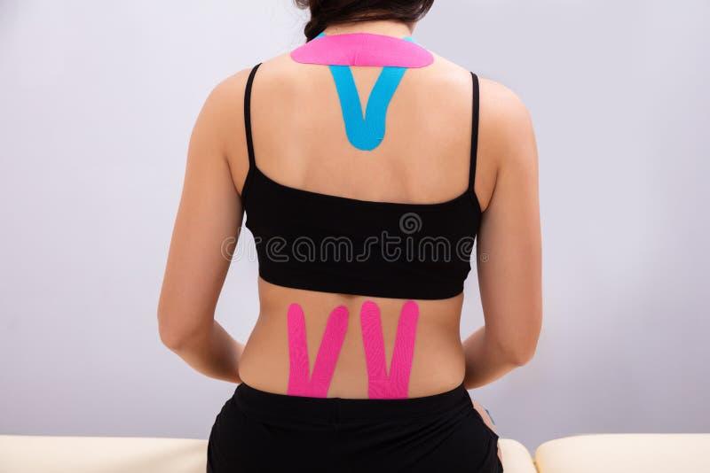 妇女背面图有理疗的磁带的 图库摄影