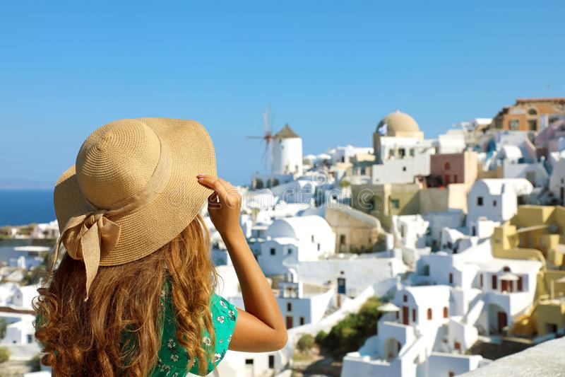 妇女背面图有看Oia村庄的帽子的在圣托里尼海岛在地中海,希腊 旅行在欧洲 免版税库存图片