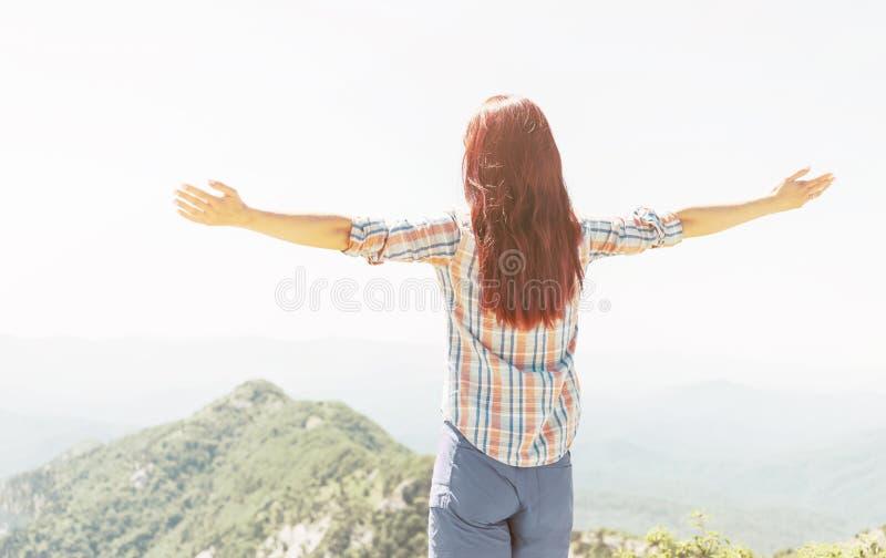 妇女背面图有被举的胳膊的在山 库存照片