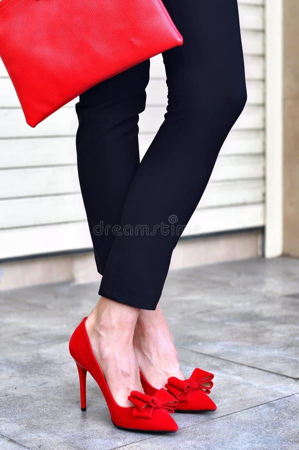 妇女腿、红色高跟鞋和袋子 塑造室外射击 图库摄影