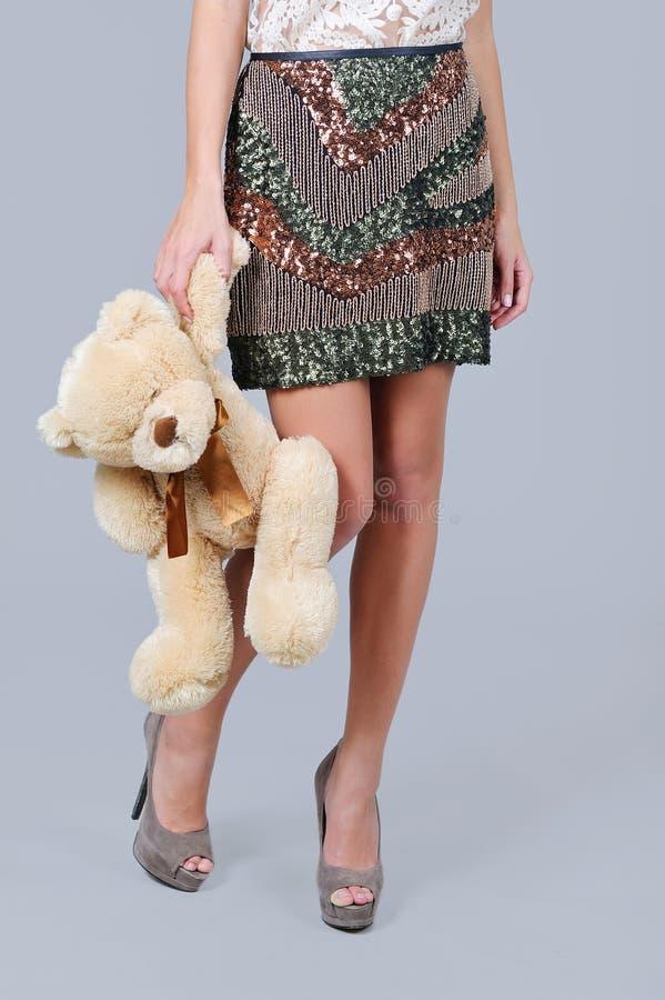 妇女腿、闪光金属片的裙子和熊戏弄 图库摄影