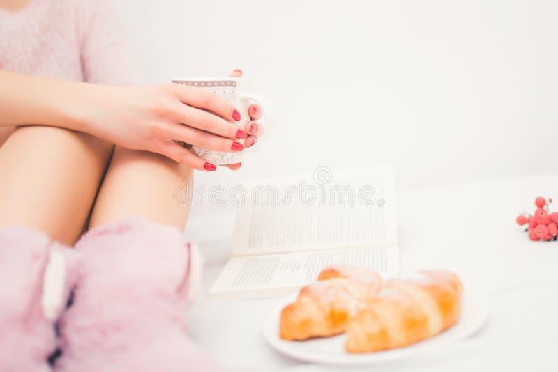 妇女腿特写镜头在床上,当蓬松拖鞋喝咖啡 图库摄影