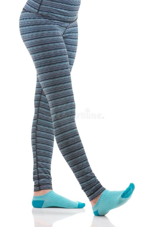 妇女腿,当舒展佩带五颜六色的蓝色和灰色镶边体育时的锻炼气喘和蓝色袜子 免版税库存照片