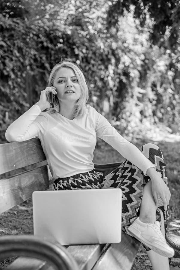 妇女膝上型计算机在公园享用绿色自然和新鲜空气 梦想的女孩利用网上购物 女孩坐长凳 免版税图库摄影