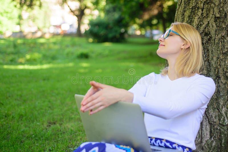 妇女膝上型计算机在网上公园研究 女孩坐与笔记本的草 女孩作为好处真正教育 需要分钟发现 免版税库存图片