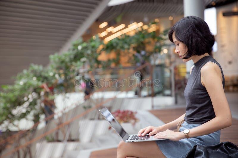 妇女自由职业者与她的手提电脑一起使用 免版税库存照片