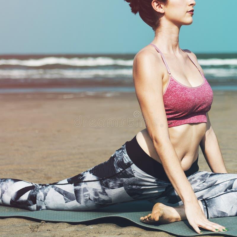 妇女舒展在海滩 免版税库存照片