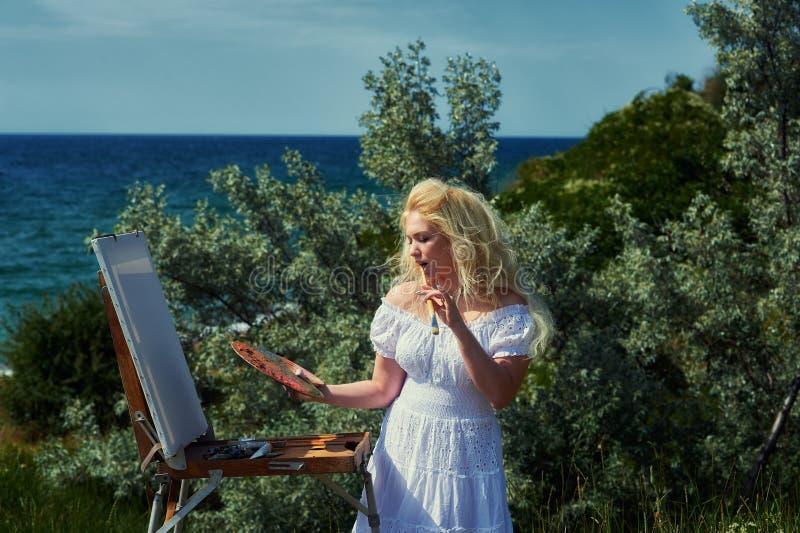 妇女艺术家参与在海滩的绘画 库存图片