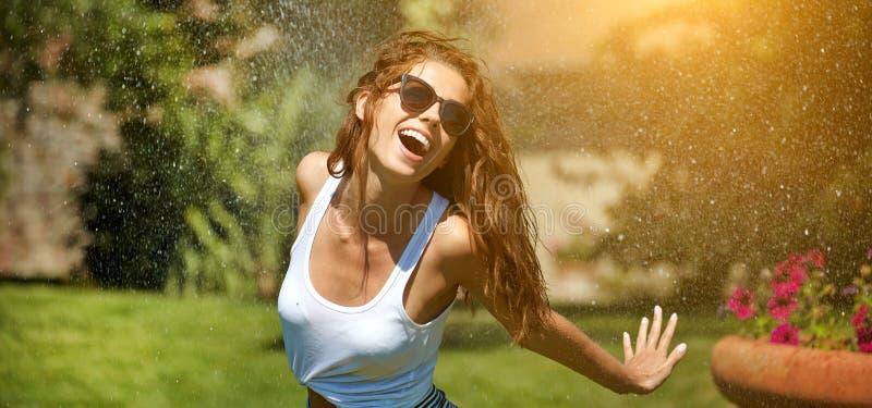 妇女获得乐趣在夏天庭院 免版税库存图片