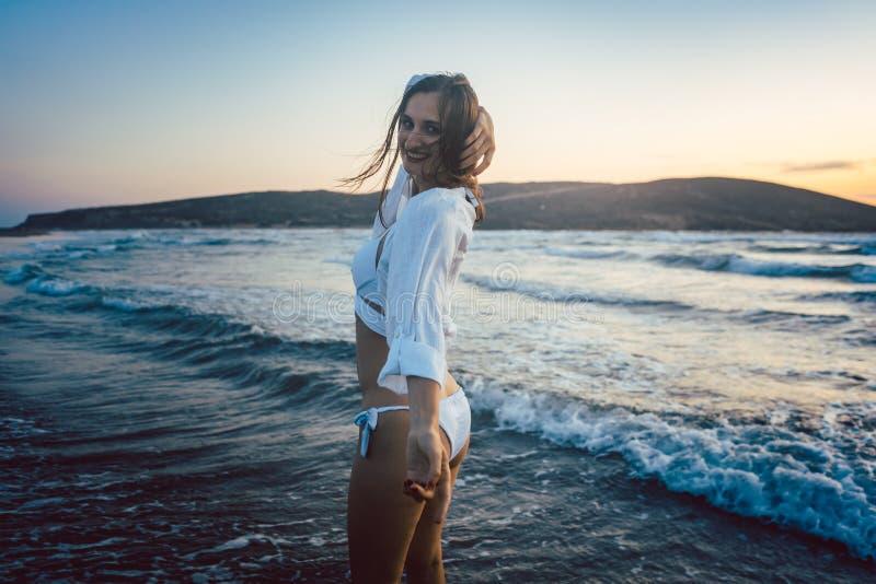 妇女获得乐趣在海滩在日落时间 库存图片