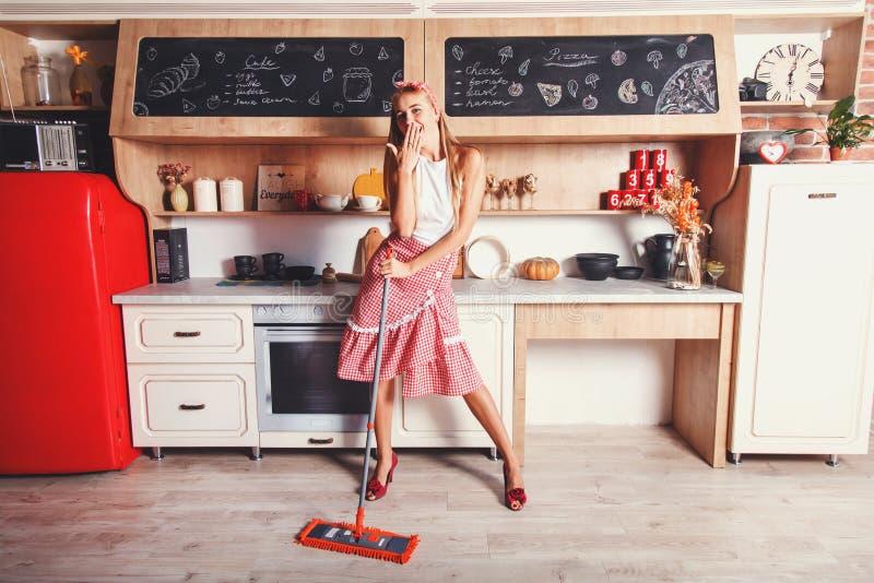 妇女获得乐趣,当做在家时清洗 免版税库存图片