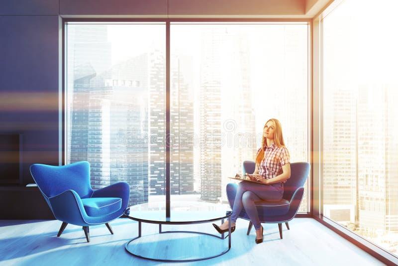 妇女蓝色扶手椅子客厅,黑壁炉 免版税图库摄影
