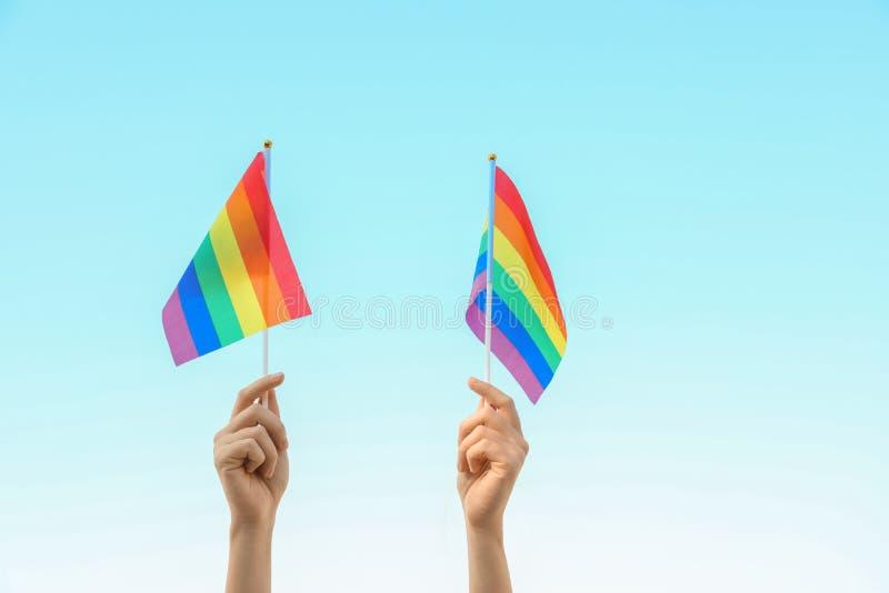 妇女藏品反对天空蔚蓝的彩虹LGBT旗子 图库摄影