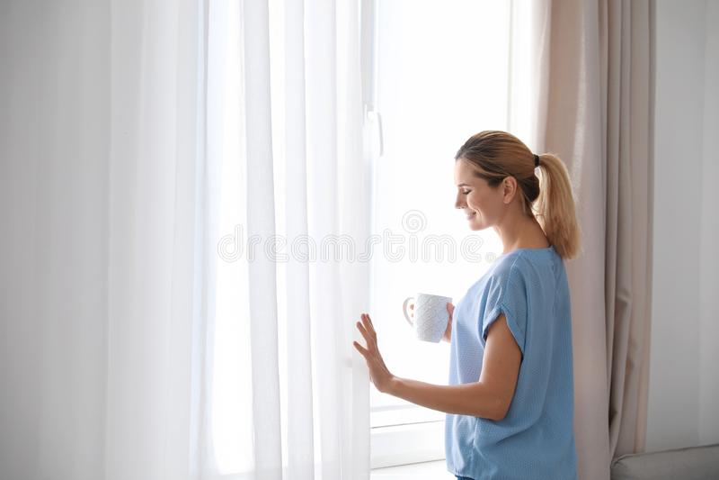 妇女藏品咖啡在窗口附近的与美丽的帷幕在家 免版税库存照片