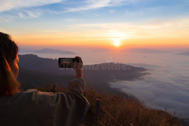 妇女藏品智能手机和接管天空和日出照片  雾和山在Phu chifa,清莱,泰国 库存图片