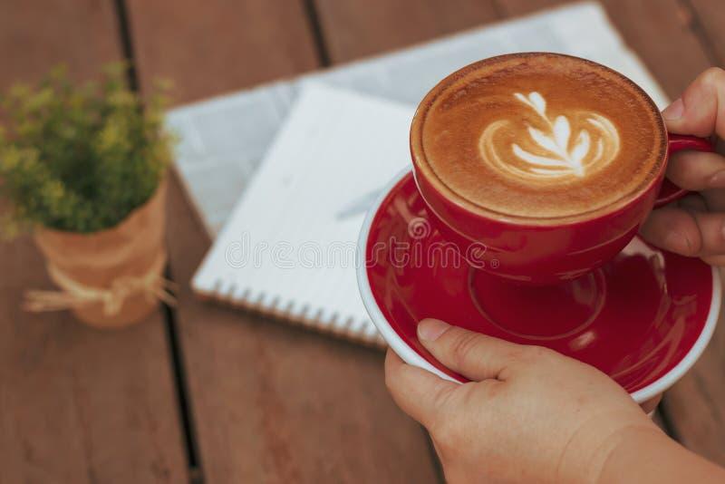 妇女藏品杯子与拿铁艺术的热的咖啡 喜爱的咖啡因饮料 茶点饮料在早晨 免版税库存图片