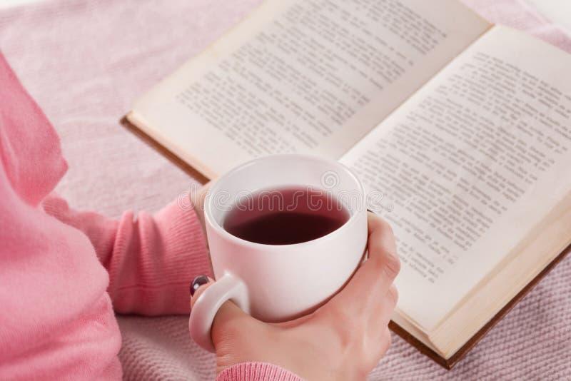妇女藏品杯子热的茶饮料和看书在家在床上 免版税库存图片