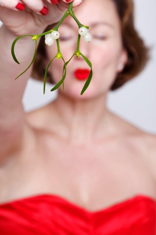 妇女藏品槲寄生亲吻 免版税库存图片