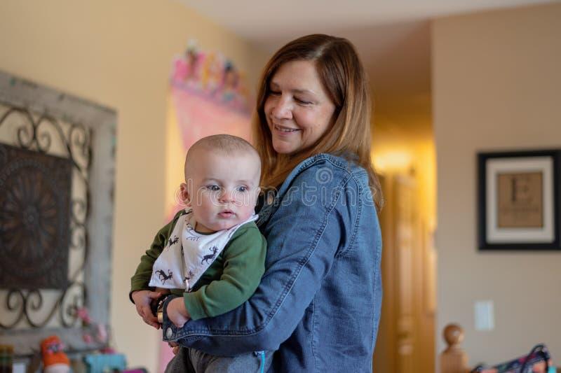 妇女藏品男婴,当参观与家庭时 免版税库存照片