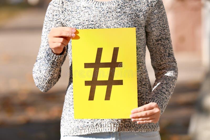 妇女藏品纸片与户外hashtag标志的 免版税库存图片