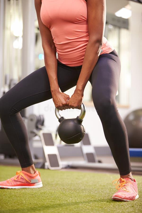 妇女行使在与kettlebell重量的一间健身房的,庄稼 库存图片