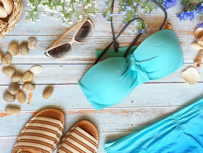妇女衣裳辅助比基尼泳装胸罩黄色短裤牛仔裤使夏天背景海滩穿戴sunglass凉鞋贝壳围巾蓝色w靠岸 库存图片