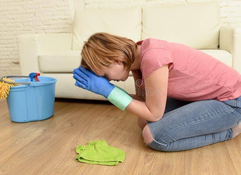 妇女被注重和疲倦清洗洗涤在她膝盖祈祷的房子地板 免版税图库摄影