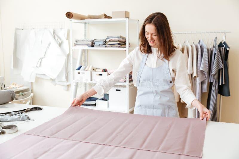 妇女裁缝传播的织品在车间 库存图片