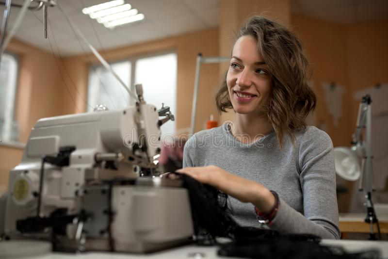 妇女裁缝在一台缝纫机工作在车间 免版税库存照片