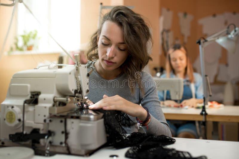 妇女裁缝在关于缝纫机的车间工作 免版税库存图片