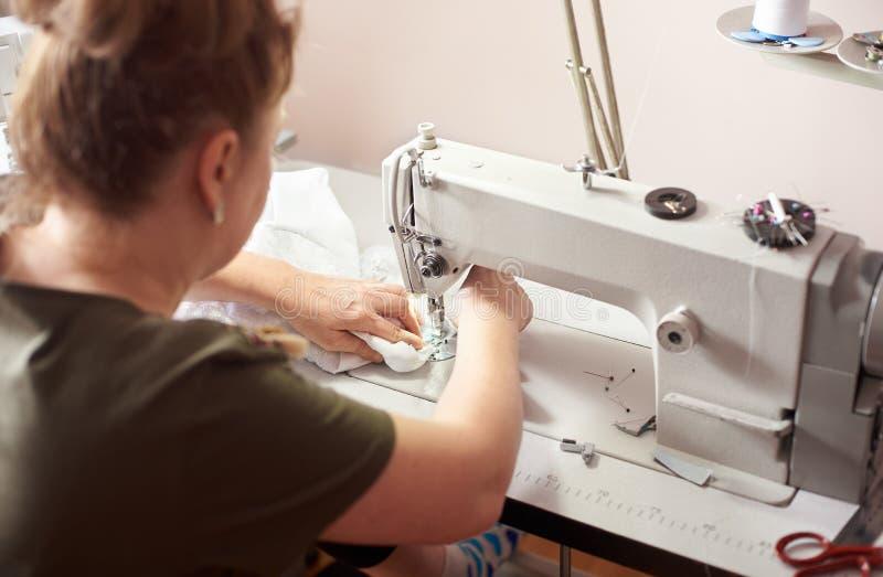妇女裁缝坐工作场所在做有专业缝纫机的工作室缝的白色礼服 r 免版税库存照片