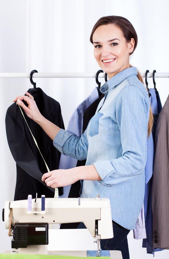 妇女裁缝measuringa衣服 免版税库存图片