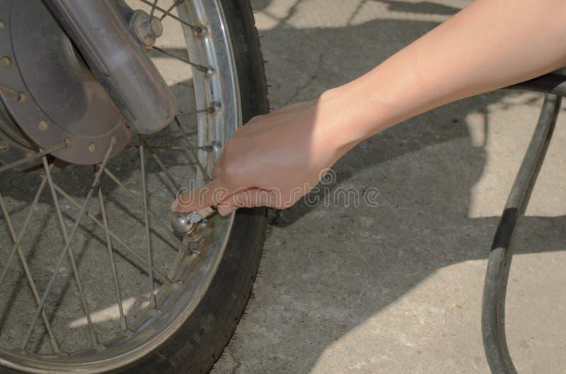 妇女装填装的空气于罐中入摩托车轮胎 库存照片