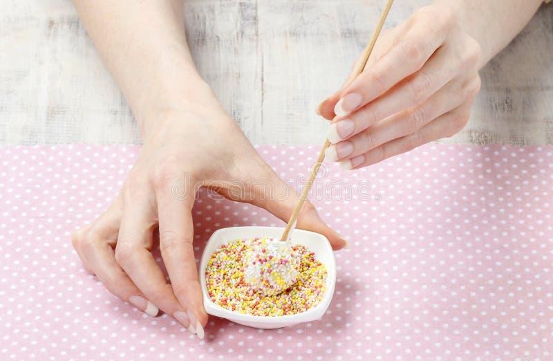 妇女装饰蛋糕与五颜六色的流行音乐洒 免版税库存照片