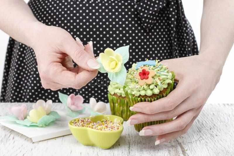 妇女装饰绿色神仙的杯形蛋糕 免版税库存照片