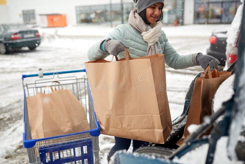 妇女装货食物从购物车到车厢 库存图片