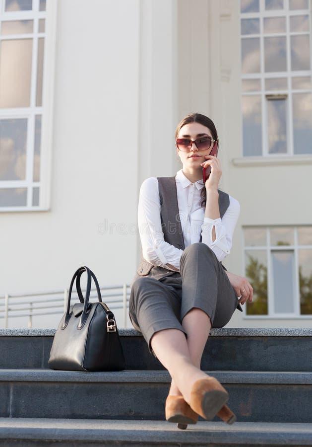 妇女西装,提包,巧妙的电话 免版税库存图片