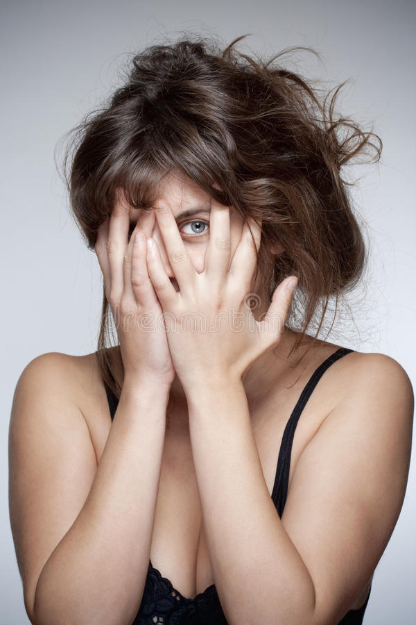 妇女覆盖物面孔用她的手 库存照片