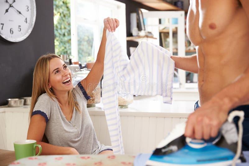 妇女观看的人电烙的衬衣在厨房里 免版税库存照片