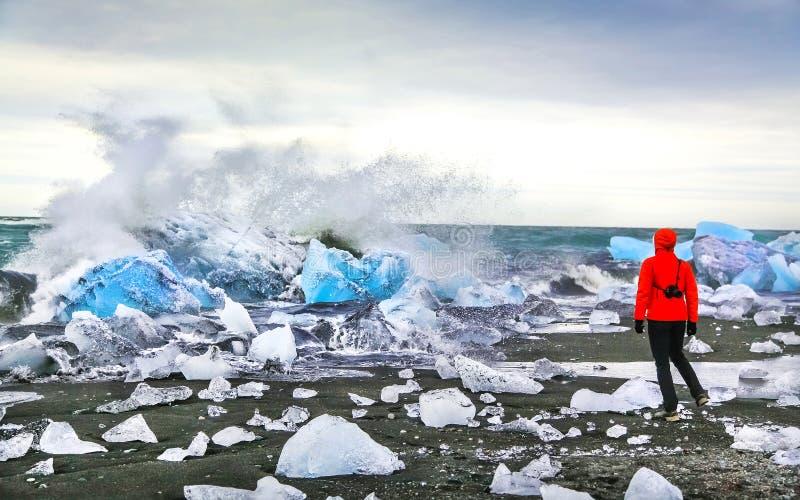 妇女观看的波浪碰撞反对冰山在Jokulsarlon冰河盐水湖在Vatnajokull国家公园,东南冰岛附近 免版税库存照片