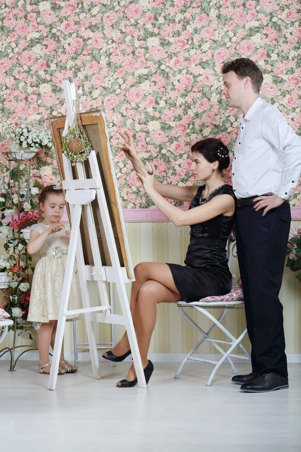 妇女解释她的计划给艺术家,并且小女孩站立 免版税库存照片