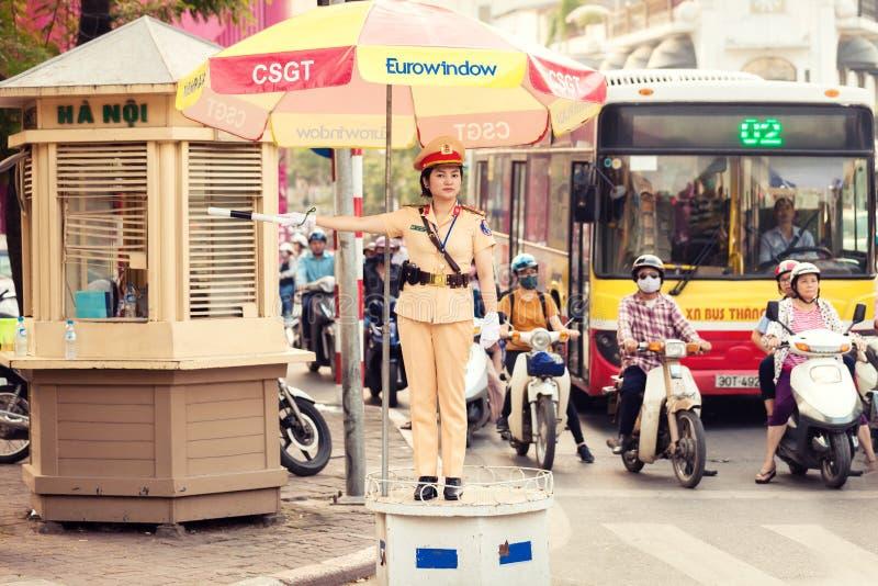 妇女警察在河内市控制在一条拥挤的街上的交通 免版税库存图片
