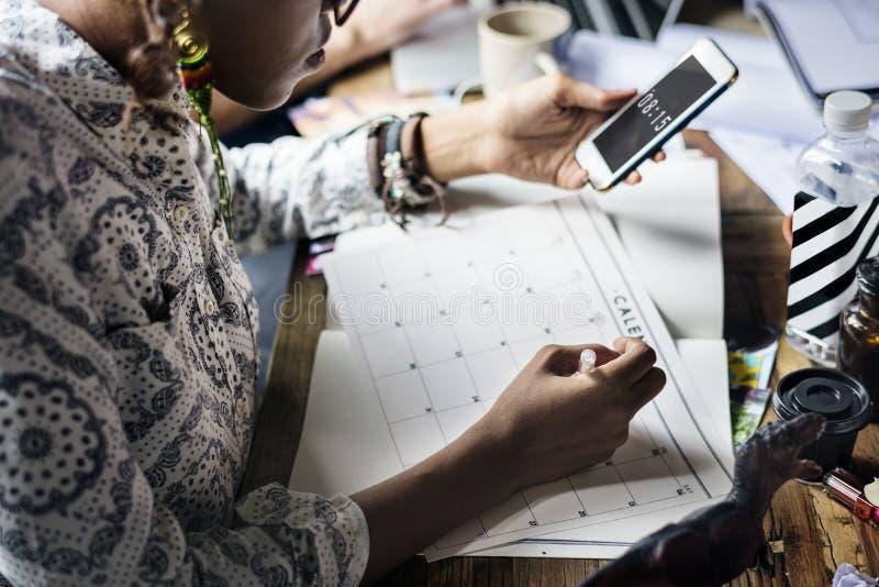 妇女计划关于日历的文字笔记 免版税库存图片
