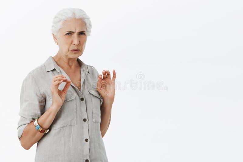 妇女认为它憎恶 做鬼脸的看见生气的资深的妇女画象有白发的皱眉和蠕动 图库摄影