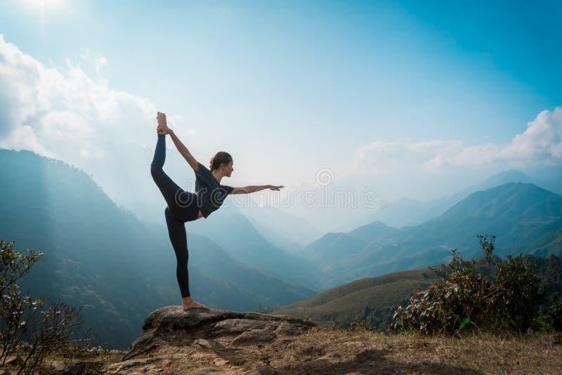 download 妇女训练瑜伽,在背景的山 库存图片.图片