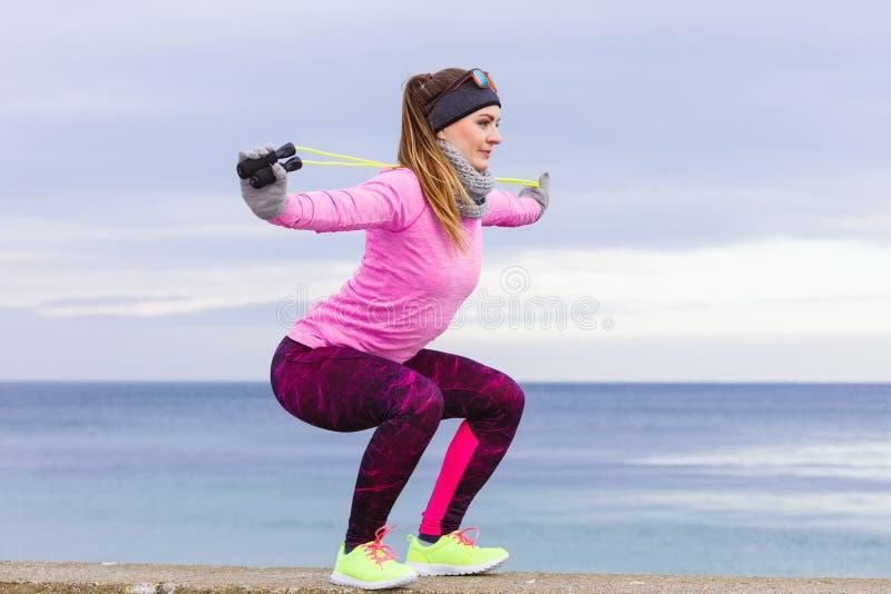 妇女训练室外与跳绳在冷的天 库存照片