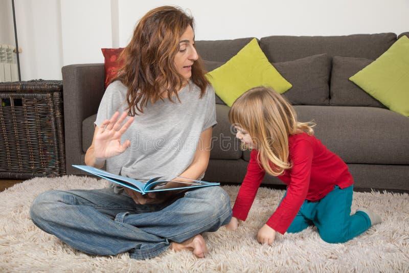 妇女讲故事对孩子坐地毯 库存图片