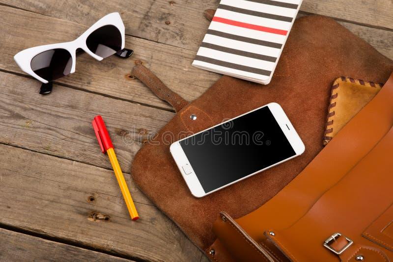 妇女设置了与袋子、巧妙的电话、太阳镜、笔记薄、笔和钱包在棕色木书桌上 免版税图库摄影