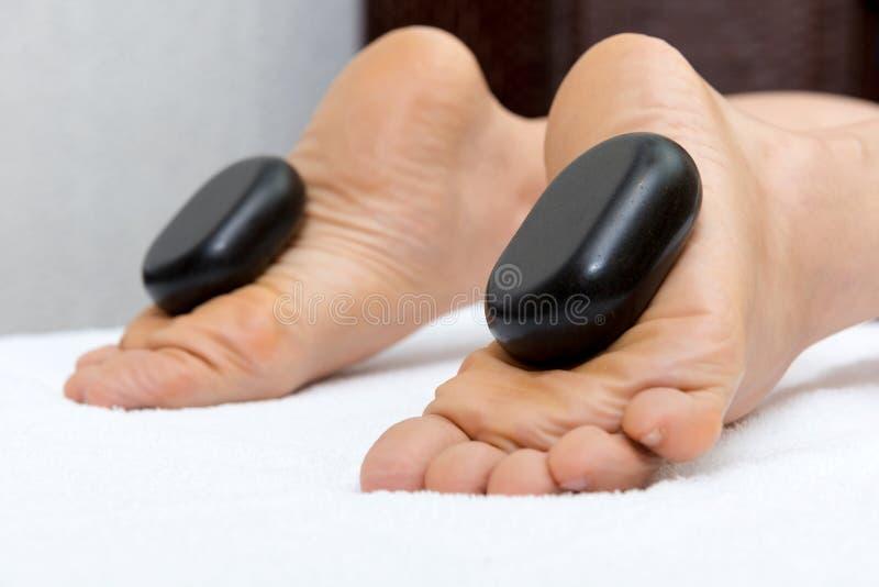 妇女说谎在胃的,做腿和脚的女性女按摩师与热的石头的按摩 图库摄影